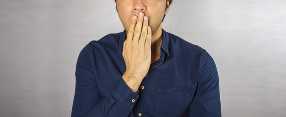 Man making hand cover mouth expression