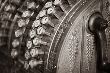 Details of keys of an old mechanical metal calculator . Sepia tint.