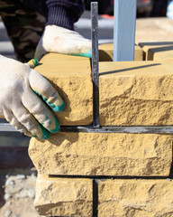 man builds a brick wall at a construction site
