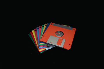A stack of colorful floppy disks on the black background