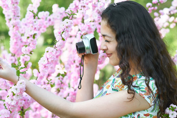 girl with camera taking pictures of pink flowers, nature beauty