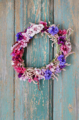 Cornflower door wreath hanging on rustic wooden background.
