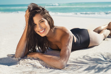 Happy woman lying on sand