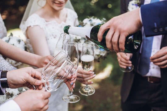 happy group of people toasting with champagne. man holding bottle of champagne and pouring drink into glasses. bride bridesmaids and groom groomsmen having fun. holiday celebration