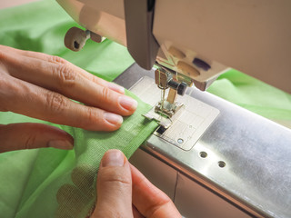 Seamstress works on a sewing machine. Stages of the production cycle on a sewing machine.