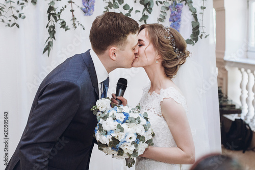 Bride With Microphone Kissing With Groom After Toast At Wedding
