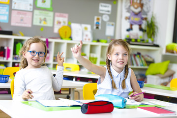 At School - Beautiful young kids have fun in school while learning in classroom