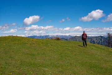 Adventurer is walking along green mountain meadow