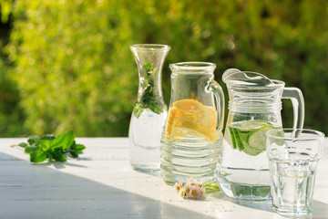 Three variants of fresh homemade lemonade with lemon, cucumber and mint. Lemonade in jugs and carafe on garden.