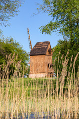 Old, vintage polish windmills, view from the lake, through reeds. Lednica lake, Poland.