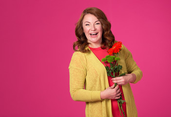 Beautiful adult woman with flowers on a pink background.