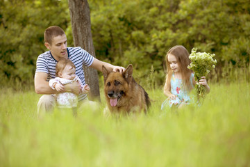 Father with two daughters and a dog, German shepherd on a background of green grass