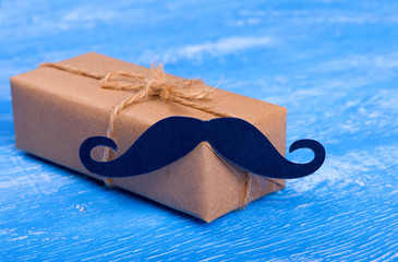 Gift box with a mustache - concept. A gift for a man. Father's Day. Barber.