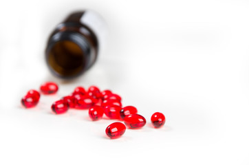 Tablets of red color vitamin E and bottle on a white background.