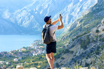 A man takes a picture on a smartphone from the mountains