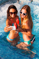 Happy girlfriend with a drink on a summer party by the pool take selfie on smartphone, summer time