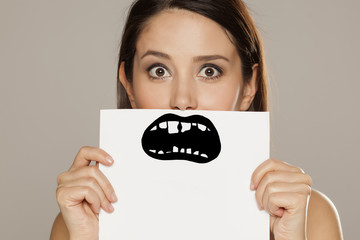young woman with bad teeth drawn on paper on gray background