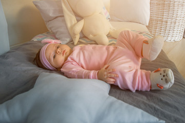 A little baby girl lies on a bed in pink clothes and a bandage on her head