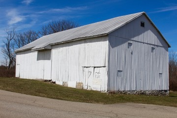 The old white barn in the country on a sunny day.