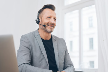 Cheerful mature man talking on headset