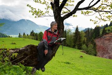 Joyful adventurer with map sits on a tree