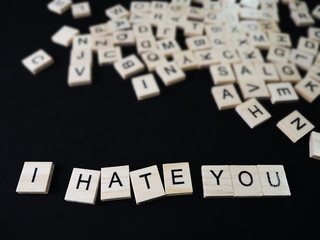 words hate text on wooden blocks on black background