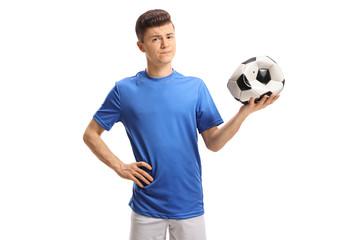 Sad teenage soccer player holding a deflated football