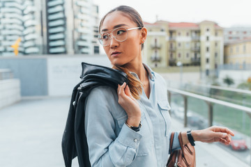 Portrait of businesswoman outdoors, carrying leather jacket over shoulder, looking away, pensive expression