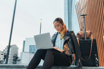Businesswoman, sitting outdoors, using laptop, wheeled suitcase beside her