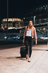 Woman walking outdoors at night, pulling wheeled suitcase