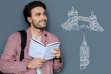Pleasant dreams. Cheerful dreamy student standing with a book in his hands and thinking about travelling abroad
