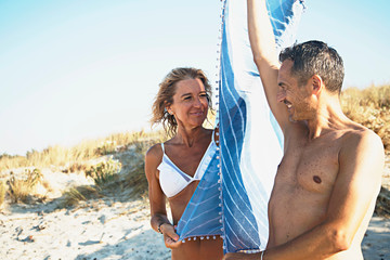 Mature couple on beach, holding beach blanket between them, smiling
