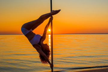 Athletic girl makes beautiful athletic, acrobatic elements on a portable pylon on the beach. Sand, sunset, beach.