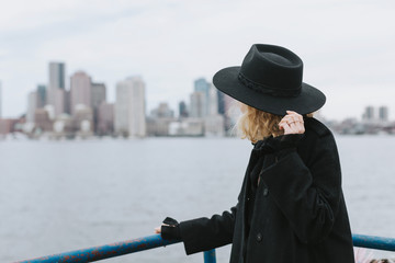 Woman wearing hat looking away at skyline, Boston, Massachusetts, United States