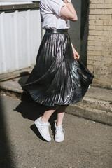 Woman in street twirling metallic skirt