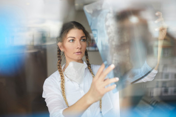 Young female doctor looking at hospital xray