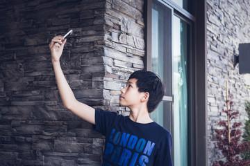 Asian teenager using mobile phone take photo selfie.