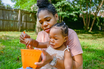 Mid adult woman playing with toy bucket in garden with baby daughter