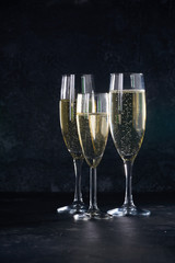 Elegant glasses of yellow champagne with bubbles on black background with reflection