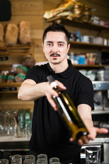 Male barista serving a bottle of wine