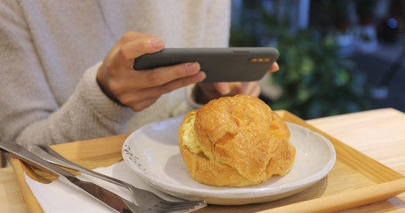 Woman taking photo on mobile phone in coffee shop