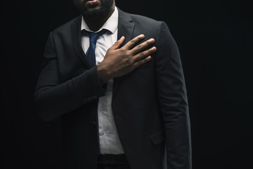 Black businessman with hand on chest