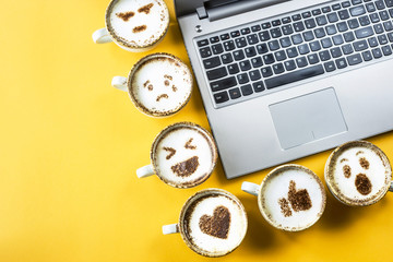 Smile emoji painted on cups of cappuccino next to the laptop on a yellow background. Emotions and communication online concept