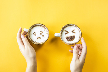 Emoji's laughter and sadness are drawn on cappuccino cups on a yellow background. Woman Emotions in social networks. Top view, flat lay