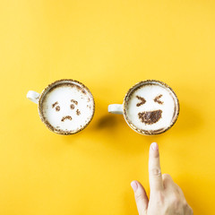 Emoji's laughter and sadness are drawn on cappuccino cups on a yellow background. Woman chooses laughter. Emotions in social networks. Top view, flat lay