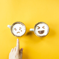 Emoji's laughter and sadness are drawn on cappuccino cups on a yellow background. Woman chooses sadness. Emotions in social networks. Top view, flat lay