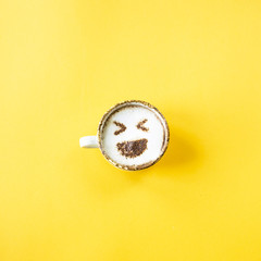 Emoji's laugh is drawn on a cup of cappuccino coffee. Emotions in social networks concept. Top view, flat lay