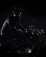 Macho, brutal biker in leather jacket riding motorcycle at night time, copy space. Man with beard, biker in leather jacket sitting on motor bike in darkness, black background. Bikers leisure concept.