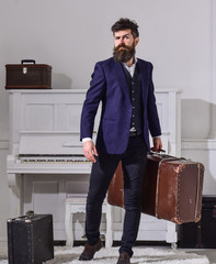 Macho stylish on strict face stands and carries big vintage suitcase. Baggage and travelling concept. Man, traveller with beard and mustache with baggage, luxury white interior background.