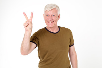 Adult man with gray hair showing fingers digit two standing isolated on white background. Gesturing two fingers sign V.